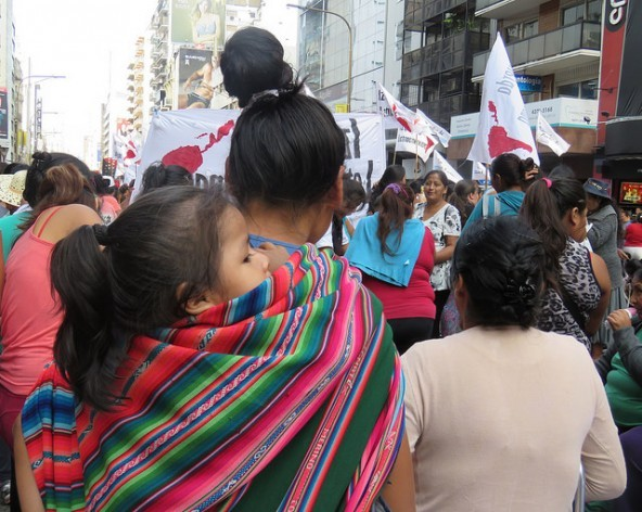 A migrant from an Andean country, carrying her daughter on her back, demonstrates for her rights along with other migrant women, in Buenos Aires, during a Mar. 24 march marking the anniversary of the 1976 military coup that ushered in seven years of dictatorship. Credit: Fabiana Frayssinet/IPS
