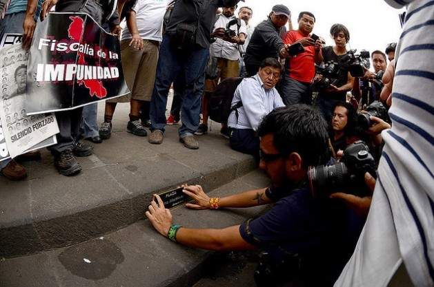 Mexican photographer Rubén Espinosa places a plaque in honour of Regina Martínez, on Apr. 28, 2015, in the central square of Xalapa, the capital of the southern state of Veracruz, to commemorate the third anniversary of the journalist's murder. On July 2015, Espinosa was also killed. Credit: Roger López/IPS