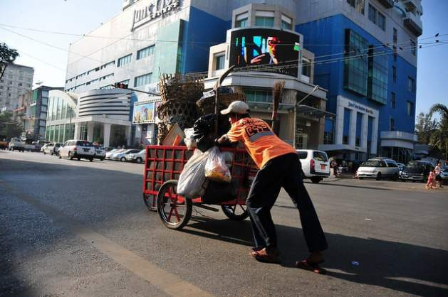 Quantitative Easing for Wealth Redistribution - A man pushes a cartful of garbage near a busy intersection in Yangon, Myanmar. Credit: Amantha Perera/IPS