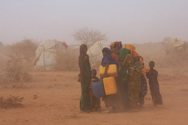 Women and children caught in a dust-laden gust at an IDP settlement 60km south of the town of Gode, reachable only along a dirt track through the desiccated landscape. Credit: James Jeffrey/IPS
