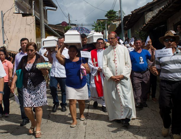 The coffins of six children killed by the Salvadoran army in May 1982 are carried through the cemetery by relatives, human rights activists and residents of the town of Arcatao, in El Salvador, on Sept 27, 2017. They had been missing for 35 years and their remains were found in January. Credit: Edgardo Ayala/IPS