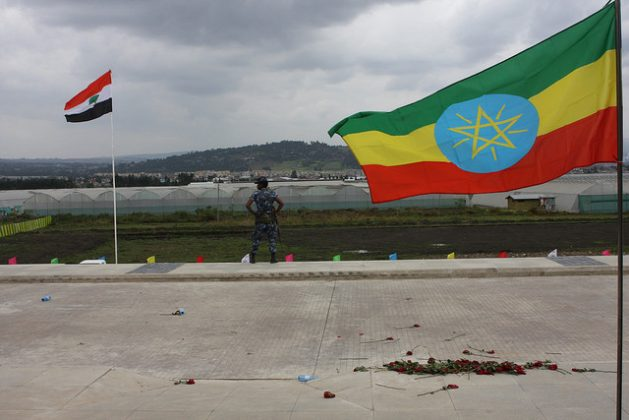 In early October 2016 a federal policeman stands guard between the Oromo regional flag (left) and Ethiopia's national flag at the ceremony marking the opening of the Addis Ababa-Djibouti railway, an apparent boon for the country's strengthening economy that at the same time angers so many Ethiopians who feel their lives are no better off despite all the economic fanfare and proclamations. Credit: James Jeffrey/IPS