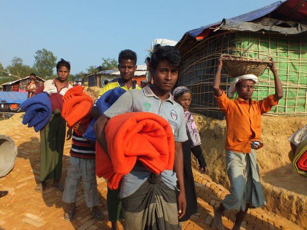 Rohingya refugees carry blankets at a camp in Bangladesh. Credit: Naimul Haq/IPS