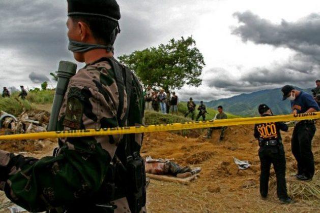 A police commando stands guard as forensics investigators unearth the victims of the Ampatuan massacre. Credit: InterAksyon file photo