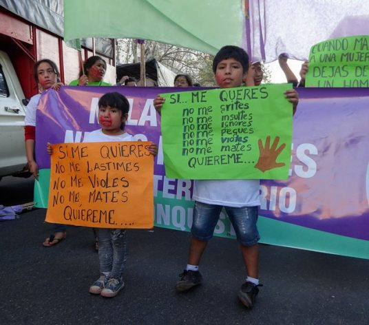 """A girl and a boy hold two posters, one of which reads: """"If you love me, do not hurt me, do not rape me, do not kill me, love me"""", during one of the demonstrations in Buenos Aires under the slogan """"Ni una Menos"""" (Not one [woman] less), held since 2015 against gender violence. Credit: Fabiana Frayssinet / IPS"""