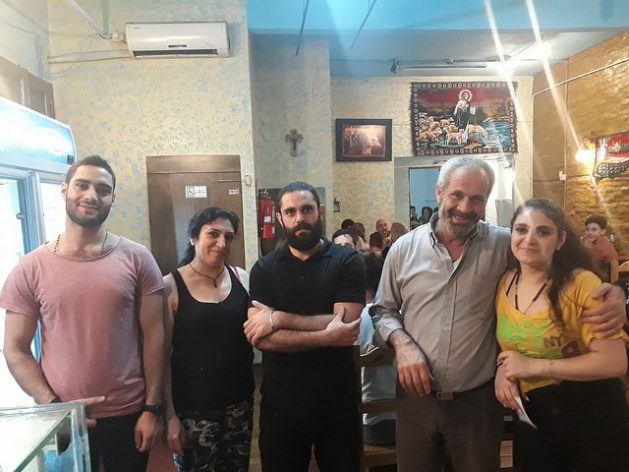 Fares, Tereza, Osama, Hatem and Nansy Badwan pose on a Saturday night in the Middle Eastern restaurant that the family runs in the Villa Crespo neighbourhood, in Buenos Aires. They moved from their war-torn country, Syria, to Argentina. When they opened the restaurant, they did not even have enough money to buy enough glasses. Credit: Daniel Gutman / IPS