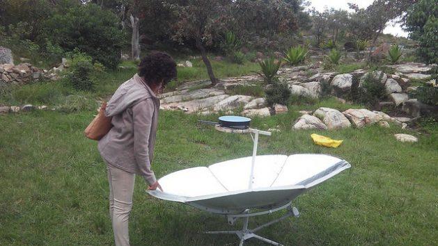 A young woman admires a parabolic solar cooker at a solar fair in Rusape, Zimbabwe. Credit: Tonderayi Mukeredzi/IPS