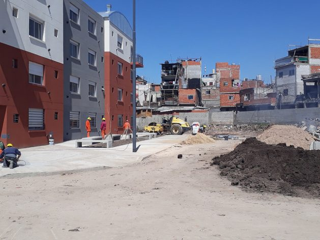 Unfinished buildings in the Pope Francis neighbourhood, a modern social housing complex, and in the background the Villa 20 shantytown, where some 28,000 people live without basic services, in the south of Buenos Aires. Credit: Daniel Gutman/IPS
