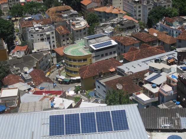 Solar panels can be seen on three buildings in the Morro de Santa Marta favela in Rio de Janeiro. In the middle is the CEPAC daycare center, with a green terrace and two sets of photovoltaic panels, which reduced its expenses by 80 percent thanks to solar energy. Credit: Mario Osava/IPS