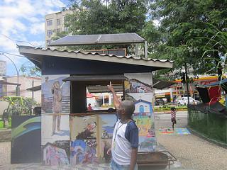 Mandundu Muziala Washiwa, um imigrante da República Democrática do Congo, agora um guia turístico no Rio de Janeiro, fica em frente à cabine de informações turísticas na entrada da favela do Morro de Santa Marta, cuja eletricidade vem de dois painéis solares. Crédito: Mario Osava / IPS