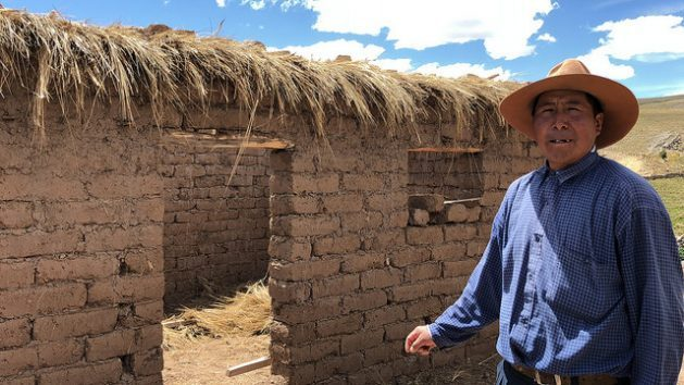 Néstor Flores, who lives in the village of Quinsalakaya, more than 4,300 meters above sea level, in the Andes highlands of southeastern Peru, stands outside his new adobe brick home, where he and his family will move before the end of the year and which will allow them to live free of cold and smoke. Credit: Annie Solis/IPS