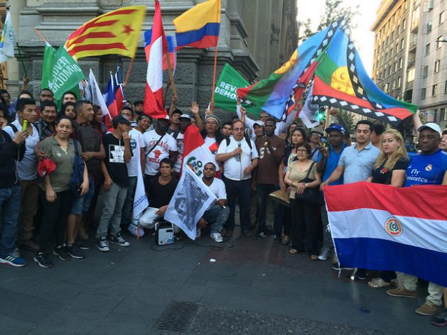 Immigrants in Chile, which draws migrants from other countries in Latin America, celebrate the Fiesta of Cultures for a Dignified Migration waving flags from their countries at the emblematic Plaza de Armas in Santiago on Dec. 18, International Migrants Day. Credit: Orlando Milesi/IPS