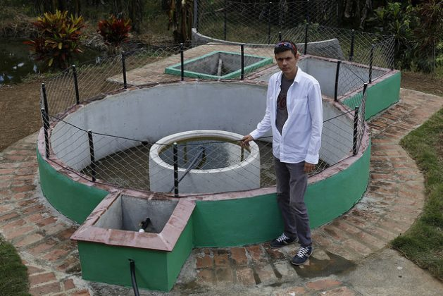 Alexander López Savrán, a 32-year-old engineer who innovated the standard fixed-dome biodigester to make it possible to create distribution networks from materials readily available in Cuba, stands next to one of these systems in the rural town of La Macuca, in Cabaiguán, Cuba. Credit: Jorge Luis Baños/IPS