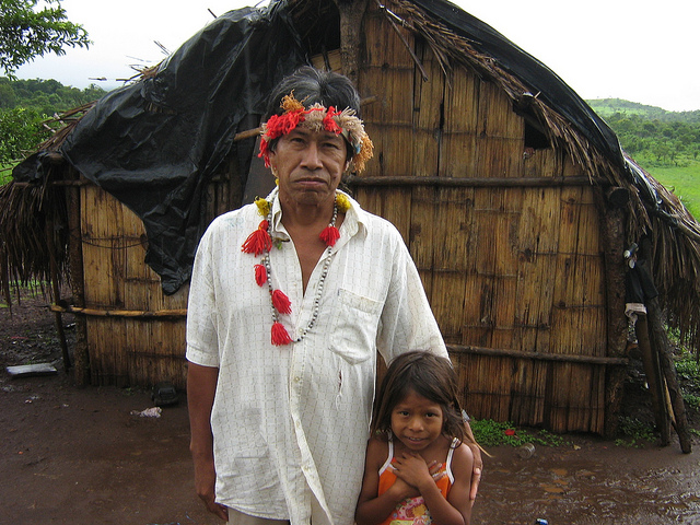 Hamilton Lopes and his daughter, members of the Guarani indigenous community, stand in front of their hut, where their family lives a precarious existence on land that has not been demarcated, where they face threats of expulsion, on Brazil's border with Paraguay. Large landowners seize the lands of the Guarani, the second-largest native community in the country, causing a large number of murders and suicides of indigenous people. Credit: Mario Osava/IPS