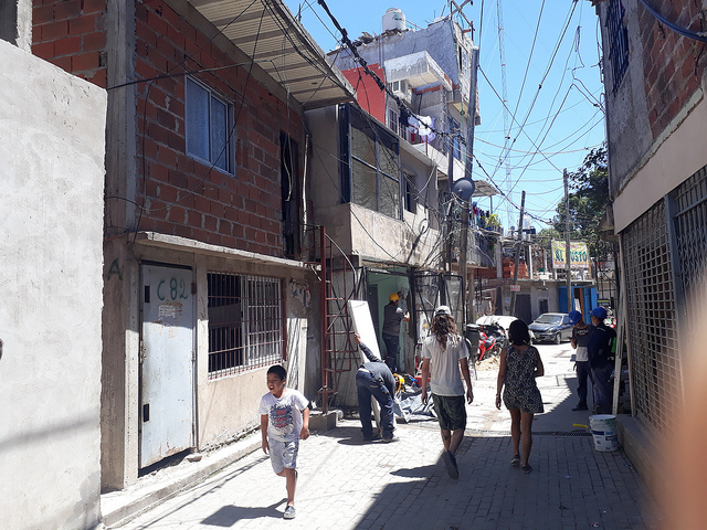A street in Villa 31, with informal dwellings up to five storeys high and tangles of electric cables unofficially connected to the grid. More than 43,190 people live in the shantytown, according to the Buenos Aires city government, which in 2016 launched an ambitious plan to urbanise the neighbourhood. Credit: Daniel Gutman/IPS
