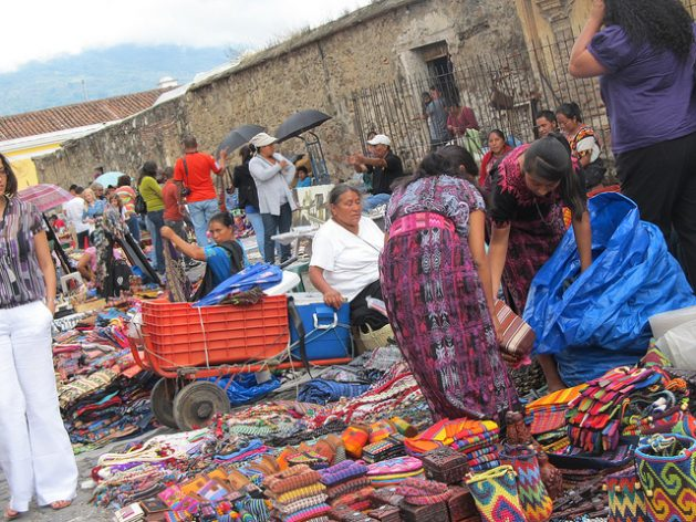 Indigenous women sell handicrafts at a street market in the tourist city of Antigua, Guatemala. Due to the continuing lack of decent employment for women in the region, many of them become street vendors, swelling the ranks of the informal economy. Credit: Mariela Jara/IPS