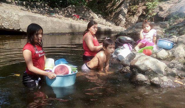 A mother washes kitchen utensils in the Aguas Calientes River, while her children play. She told IPS that this small river, part of the watershed of the Lempa River - the longest in El Salvador - always had an abundant flow, but now due to climate change and the use of water for the irrigation of sugar cane, the water level is down. Credit: Edgardo Ayala/IPS