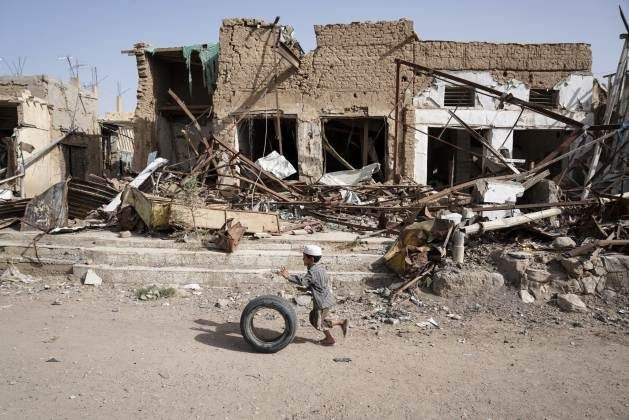 A young boy runs with his tyre past buildings damaged by airstrikes in Saada Old Town; Yemen. Credit: Giles Clarke/OCHA