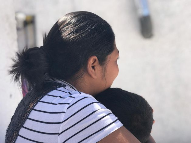 """""""Carmen S."""" holds her son, 3, at a shelter where they were staying in Ciudad Juárez, Mexico, May 2019, after being returned to Mexico under the Trump administration's """"Migrant Protection Protocols."""" Carmen told Human Rights Watch that she was thinking of trying to cross illegally but was afraid of losing her children. © 2019 Clara Long/Human Rights Watch"""