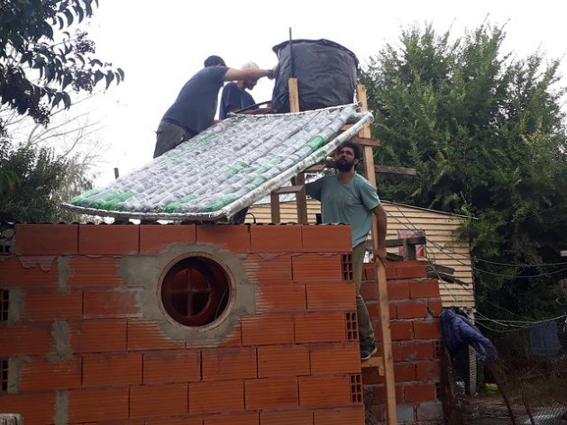 Volunteers install a solar water heater, made from recycled materials, with a 90-litre tank on the roof of a modest home in the Argentine municipality of Pilar, 50 km north of Buenos Aires. This unique thermal generation system was designed by Brazilian engineer José Alano, who did not patent it in order to facilitate its free use. Credit: Daniel Gutman/IPS