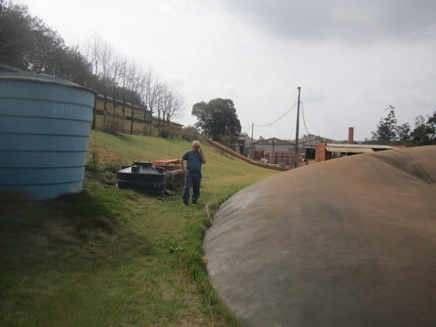 Romário Schaefer, 65, stands between the biodigester buried in the ground on the right and the blue tank holding whey that is mixed with the manure of the pigs he fattens in a row of pig pens (top left) to produce biogas, in the southern Brazilian municipality of Entre Rios do Oeste. In the background is his brick factory, which saves about 6,500 dollars a month in electricity by using biogas. Credit: Mario Osava/IPS