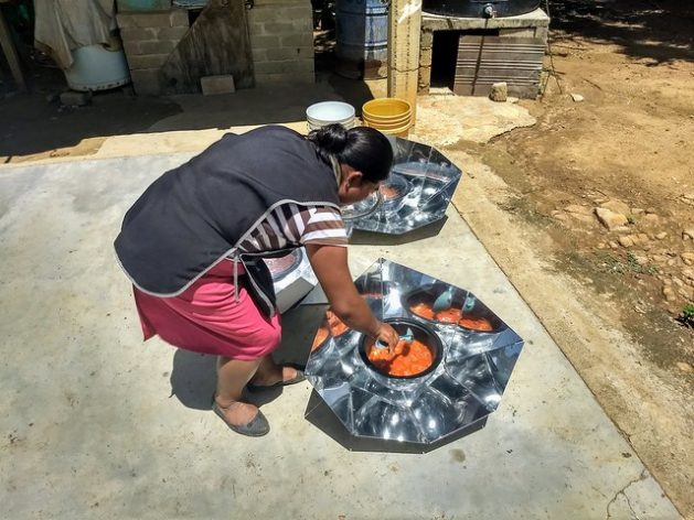 Reyna Díaz checks the marinated pork she is cooking in a solar cooker at her home in a poor neighbourhood of Vicente Guerrero, Villa de Zaachila municipality, in the southwestern Mexican state of Oaxaca. The use of solar cookers has made is possible for 200 local women to save on fuel and stop using firewood, providing environmental and health benefits. Credit: Emilio Godoy/IPS