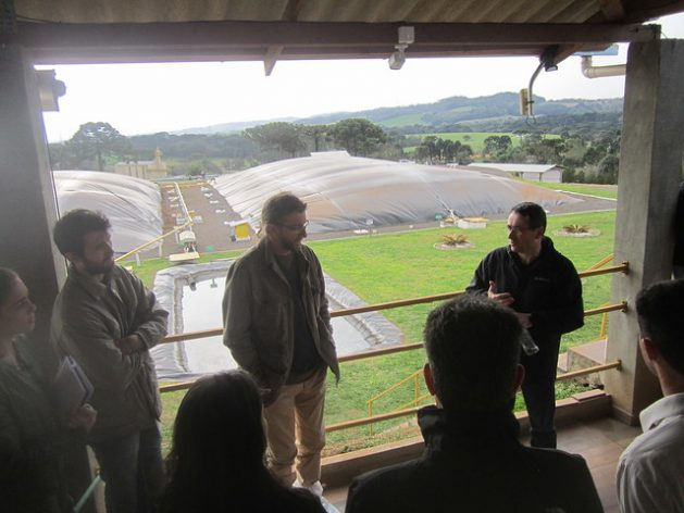 Airton Kunz, head of Research at Embrapa Pigs and Poultry, explains to visitors the Effluent Treatment System of the São Roque Pig Farm, part of which can be seen behind him, in Videira, in the southern state of Santa Catarina, Brazil's largest producer and exporter of pork. Biogas, bioelectricity and biomethane are by-products arising from the need to dispose of pork manure in an environmentally friendly manner. Credit: Mario Osava/IPS