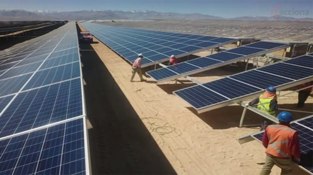 Employees work on the solar panels of the El Romero plant, with a capacity of 196 megawatts, in the desert region of Atacama in northern Chile, a country that has set out to develop its solar power potential. CREDIT: Acciona