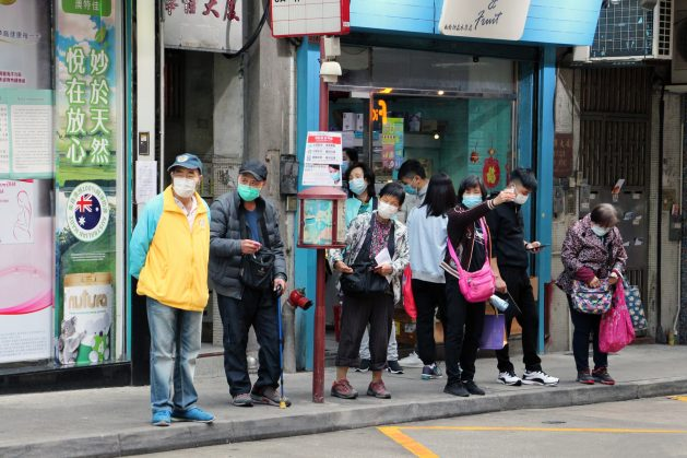 People wearing face masks at a Bus stop in Macau, China near a public hospital. This week's 73rd World Health Assembly had member states adopt a resolution to review the global response to the coronavirus pandemic. Photo by Macau Photo Agency on Unsplash