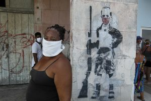A woman wearing a mask to protect herself from the contagion of the coronavirus, waits to buy food outside a store in the Playa municipality, in Havana, Cuba. As of Tuesday, Jun. 16, 1.7 million people have been affected by the virus across Latin Americaand the Caribbean -- doubling in the last week. Credit: Jorge Luis Baños / IPS
