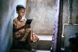 A girl in Bhubaneswar slums, India checks her e-learning assignments on a computer tablet. Courtesy: John Marshall/Aveti Learning