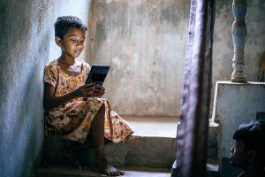 A girl in Bhubaneswar slums, India checks her e-learning [...] <a class=