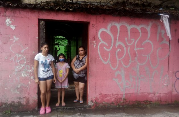 Jennifer Maldonado (I), her little sister and Carmen Carbajal, at the entrance to her home in San Salvador. They hung a white flag as a sign that they had run out of food during the quarantine adopted by the government since March 21 to contain the COVID-19 infections, as did many families in El Salvador and neighbouring Guatemala. This year marks the 25th anniversary of the Beijing Declaration and Platform for Action. It was supposed to have been a ground-breaking year for gender equality, but the coronavirus pandemic has instead widened inequalities for girls and women across every sphere. Credit: Edgardo Ayala / IPS