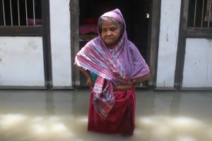 Manju Begum, 85, stands in front of her flooded house in Medeni Mandal in Munshiganj District, central Bangladesh. She says she has not received any assistance from local officials since her home was flooded more than a week ago. With nearly 5.5 million people people across Bangladesh affected by severe flooding, humanitarian experts are concerned that millions of people, already badly impacted by COVID-19, will be pushed further into poverty. Credit: Farid Ahmed/IPS