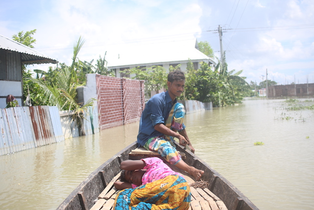 Arif Hossain on his boat on a flooded street in Lohajang in District, central Bangladesh. The former tailor now earns a living from ferrying people on his boat. People across Bangladesh have been marooned, their homes damaged and crops destroyed by the floods. Credit: Farid Ahmed/IPS
