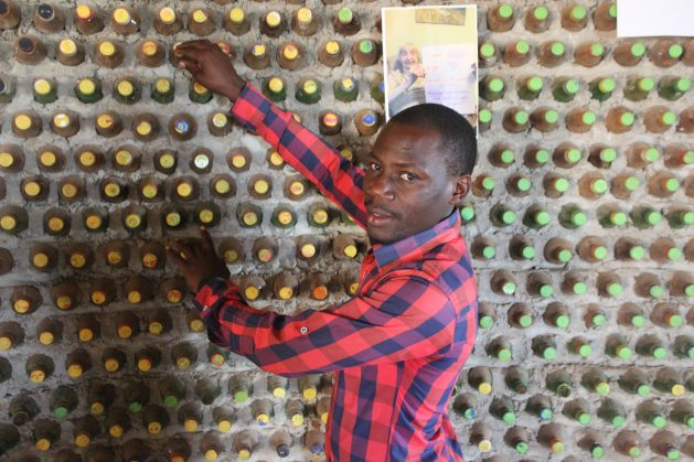 David Mande shows the walls of a house made out ecobricks. The ecobricks, according to Mande, are filled with moist soil to ensure that they become hard. The bottle top is then tightly closed to ensure that the moist sand and soil bond to make a brick that can be turned into a strong wall. Credit: Wambi Michael/IPS