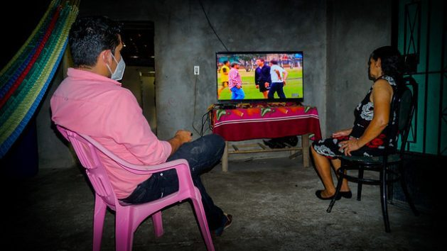 Benilda Membreño and her son Jaime Márquez enjoy a television programme, a luxury before 2006, when the village of Potrerillos in the eastern Salvadoran department of San Miguel lacked electricity. With the technical and financial support of national and international organisations, the inhabitants of Potrerillos were able to install a mini community hydroelectric plant. CREDIT: Edgardo Ayala/IPS