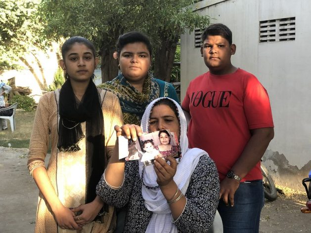 Rita Raja, pictured here with her children, holds up photos of her 13-year-old who had allegedly been abducted and forced to covert her religion and marry her 44-year-old Muslim neighbour. Credit: Zofeen T. Ebrahim/IPS