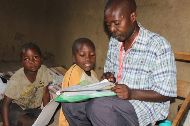 A parent helps his children to go through work received in the study kits distributed by Education Cannot Wait (ECW) implementing partners in Uganda. ECW allocated $1 million in emergency funds to its education partners in Uganda to ensure that refugee children still continued schooling despite the nationwide coronavirus lockdown. Credit: Wambi Michael/IPS