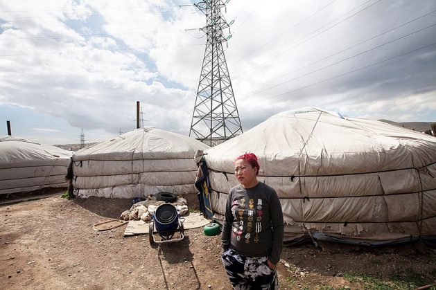 A woman stands outside a yurt in Ger District, Ulaanbaatar, Mongolia. There is power plant nearby but the government says it aims to reach net-zero emissions by 2050. Courtesy: CC BY-SA 4.0/Nathalie Daoust