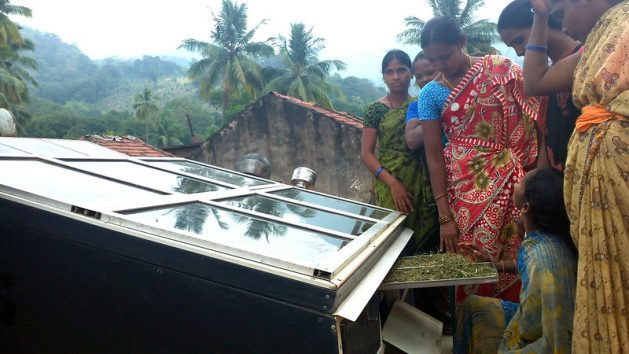 Forest women in Anantagiri forest in the south-east of India check out their solar dryer. (file photo) There is a growing shift and awareness in mainstream political, corporate and public debate about the need for climate action. Credit: Stella Paul/IPS.