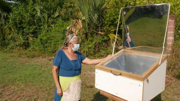 María Luz Rodríguez stands next to her solar oven where she cooked lasagna in the village of El Salamar in San Luis La Herradura municipality. In this region in southern El Salvador, an effort is being made to implement environmental actions to ensure the sustainable use of natural resources. CREDIT: Edgardo Ayala/ IPS