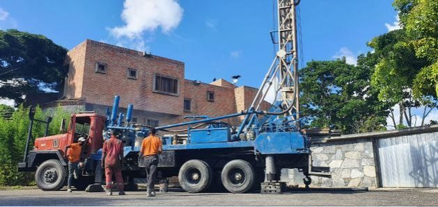 A truck with a crane is positioned next to a house to start drilling a well in search of water, which is abundant under the ground in the Caracas valley. CREDIT: Courtesy of José Manuel García