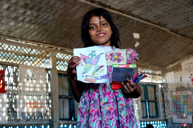 A Rohingya girl proudly holds up her drawing at a UNICEF school at Balukhali camp, Bangladesh.As Rohingya refugee families settled in the Cox's Bazar Kutupalong Refugee Camp, the area had one of highest rates of primary and secondary age children out of school. Education Cannot Wait (ECW), the multilateral global fund dedicated to education in emergencies and protracted crises, immediately allocated US$3million to urgently scale up learning spaces for displaced Rohingya children. In 2018, the Fund increased its support with an additional US$12 million for the continuous learning of refugee and host community children. (file photo) Credit: Farid Ahmed/IPS