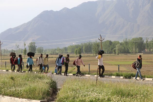 Migrant labourers wait in queues in Kashmir in order to travel back to their homes. The second wave of COVID-19 in India has seen masses of people leave cities and towns to return to their rural homes. Credit: Umer Asif/IPS