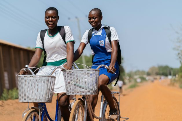 Sarah and Doris ride to school on their bicycles because they live several kilometres away. Ghana's education sector was one of the hardest affected by the pandemic and for many girls, particularly those in rural areas, the consequences of school closures means many will never return to their schooling. Credit: Jamila Akweley Okertchiri/IPS