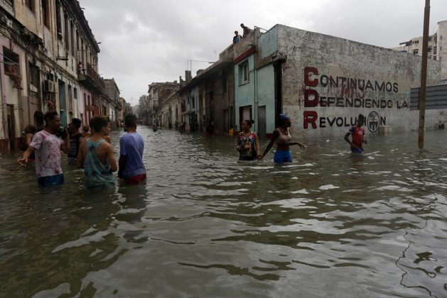 Local residents stand in the water on a street flooded by the sea in the Centro Habana municipality in the Cuban capital in September 2017 in the wake of Hurricane Irma, one of the most intense storms in recent decades in this Caribbean island nation. CREDIT: Jorge Luis Baños/IPS