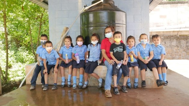 Angélica María Posada, teacher and principal of the school in the village of El Guarumal, in the municipality of Sensembra, in the department of Morazán, in eastern El Salvador, poses with some of her primary school students in front of the tank that supplies drinking water to the school and also to 150 families in this and other neighboring villages. Rainwater is collected on the tin roof and channeled into an underground tank. It is then pumped to a station where it is filtered and purified, before flowing into the tank, ready for consumption. Credit Edgardo Ayala