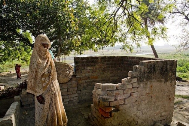 A Dalit woman stands outside a dry toilet located in an upper caste villager's home in Mainpuri, in the northern Indian state of Uttar Pradesh. A caste-based profession, manual scavenging condemns mostly women, but also men, to clean human excreta out of dry latrines with their hands, and carry it on their heads to disposal dumps. Many also clean sewers, septic tanks and open drains with no protective gear. Credit: Shai Venkatraman/IPS