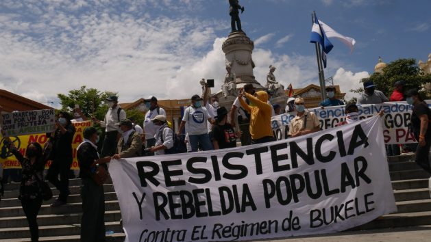"""""""Resistance and Popular Rebellion"""" reads a banner held by demonstrators in San Salvador in a Wednesday, Sept. 15 protest against measures they consider authoritarian adopted by the government of President Nayib Bukele. The latest was the replacement of the constitutional court judges by the ruling party, which paves the way for Bukele to seek immediate reelection, banned up to now in El Salvador. CREDIT: Edgardo Ayala/IPS"""